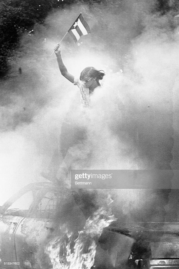 While a Newark Plice Department patrol car burns, a young Puerto Rican holds a small flag high over the wreckage near Branch Brook Park as a Puerto Rican folk festival turned violent. Mayor Kenneth A. Gibson will meet today with members of the city's Puerto Rican community.
