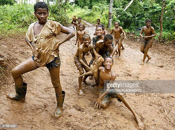 While adults prepare to cast their ballots at a nearby polling station children slide through the mud beside the ramshackle settlement of Kalabo on...