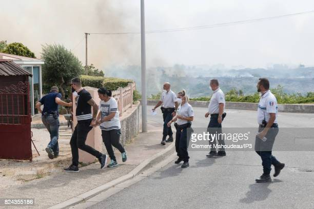 While Firefighters intervene to extinguish the fires in the South of France Police Officers help the population on July 26 2017 in Martigues France...