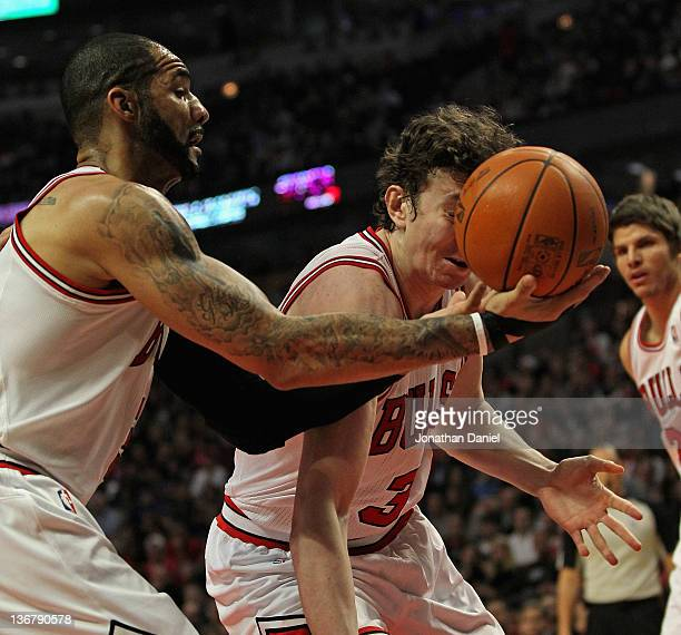 While grabbing a rebound Carlos Boozer of the Chicago Bulls hits teammate Omer Asik in the face with the ball against the Washington Wizards at the...