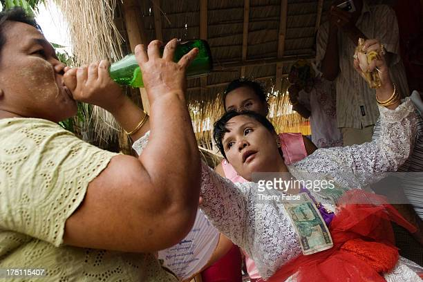 While holding a piece of chicken in a hand a medium in trance pours beer into a woman's mouth in order to appease the nat possessing that woman Every...