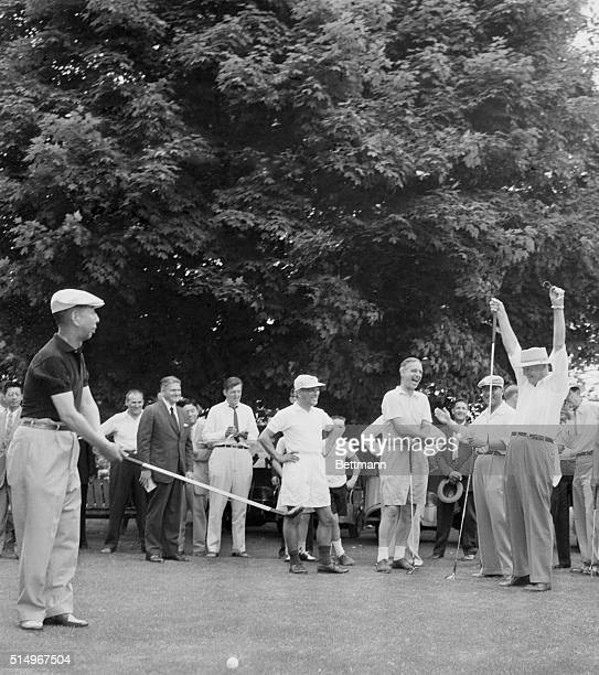 While Japanese Prime Minister Nabusuke Kishi swings a club on the first tee at Burning Tree Country Club President Eisenhower throws with hands into...