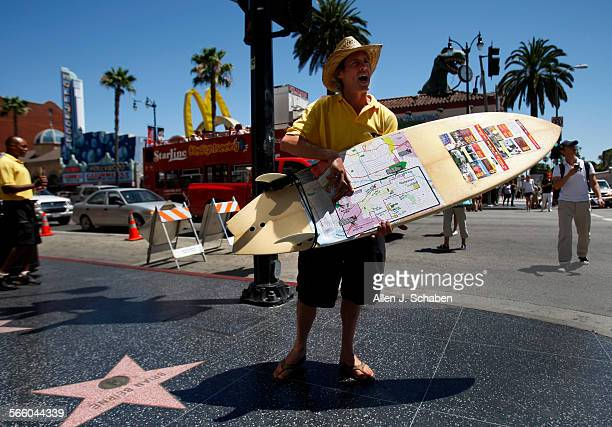 While the competing Hollywood tour company Starline Tours bus passes by in the background City Sights LA employee Chris Uhler uses a surfboard to...
