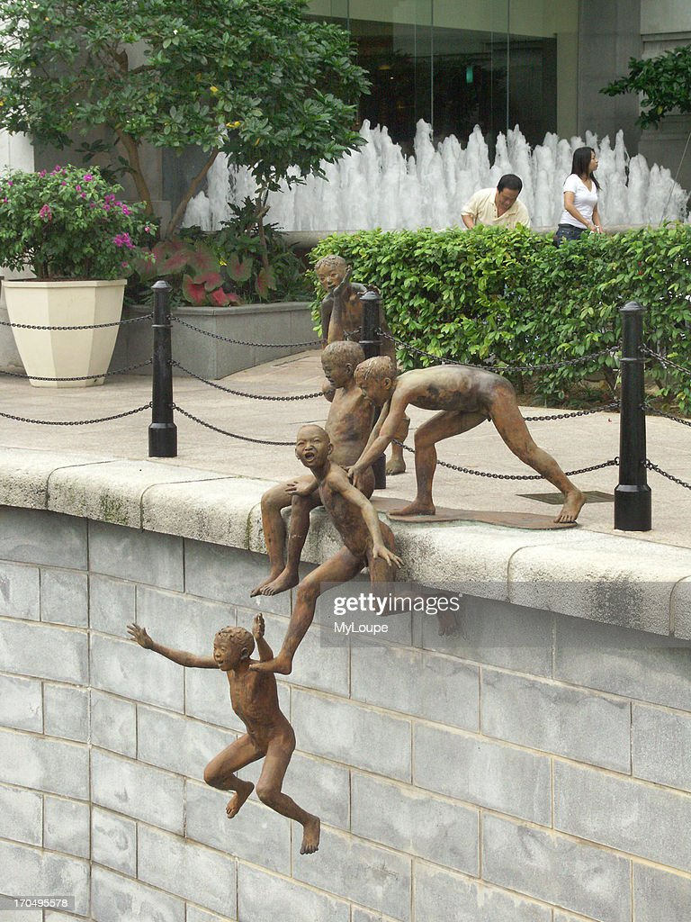 Whimsical Statue Of Children Swimming On The Bank Of The Singapore River In Singapores Commercial And Financial Area