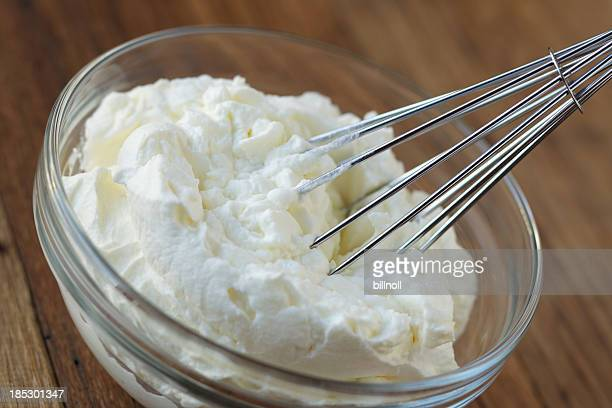 Whipped cream and whisk in glass bowl