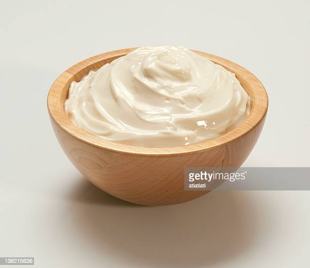 Whipped cream in light wooden bowl on white backing