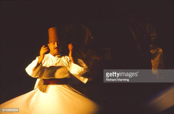 A Whirling Dervish from the Al Kindi Ensemble from Damascus in Syria performing at the South Bank Centre in London Whirling Dervishes stare at their...