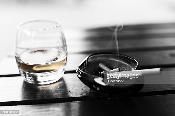 Whiskey and cigarette in an ashtray on a table