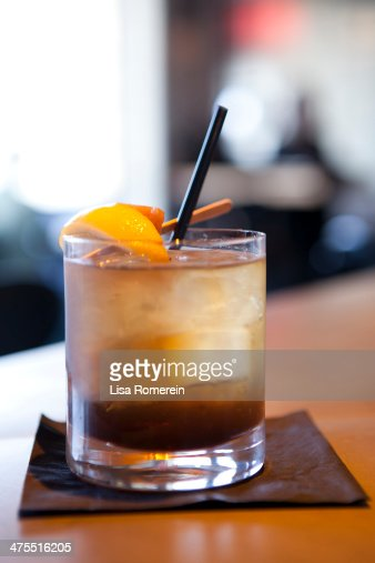 A whiskey cocktail on ice with a straw and lemon