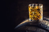 Whiskey drink. Glass of whiskey on old wooden barrel.