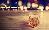 Whiskey drink on wooden dark background