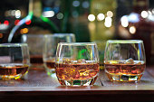 whiskey drinks with ice on wooden background
