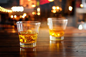 Whiskey glass drink with ice cube on wooden table in colorful night bar