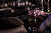 an old man hand holding a glass of whiskey at a dark seedy bar counter, with shallow depth of field