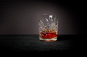 Whiskey (or whisky) in a luxury heavy cut crystal glass tumbler on a slate surface against a dark background
