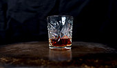 Whiskey (or whisky) in a luxury heavy cut crystal glass tumbler on a wooden table against a dark background