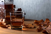 Whiskey and dried up oak leaves on a old wooden table. Copy space .