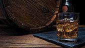 Glass and bottle of whiskey on wooden bar counter near oak whiskey barrel. Black background