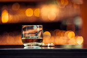 Glass of whiskey on a wooden table bar on the background of bright lights of the bar