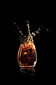Photo of a glass of alcohol with splashing liquid. The photo could represent rum, whiskey, bourbon, tea or coke.