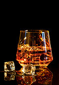 Whiskey with ice in glass on black background
