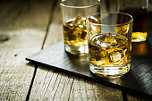 Whiskey with ice in glasses, rustic wood background, copy space