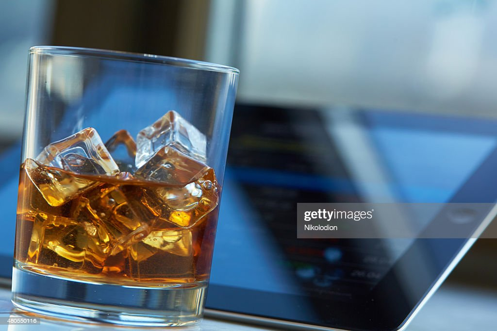 whiskey with ice, the tablet on a table : Stock Photo