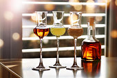 Whisky and liqueur in front of a window with sun reflexes