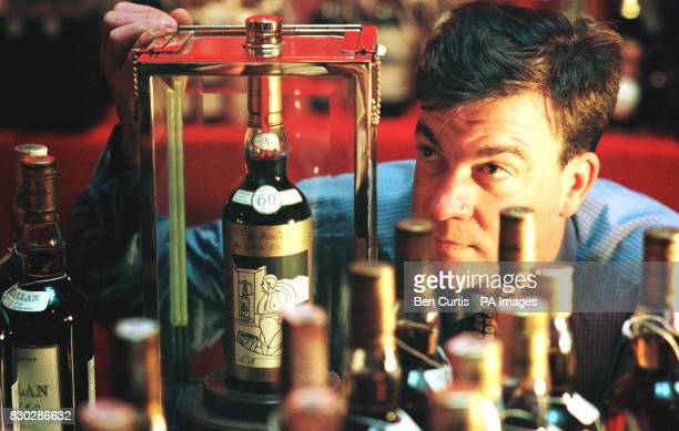 Whisky consultant Martin Green from Christies Auction House inspects an extremely rare 60yearold bottle of 'The Macallan' whisky distilled in 1926...