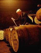 Whisky distillation, blender taking sample from storage cask