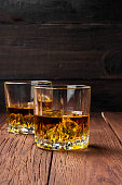 Whisky with ice in two glasses on a wooden background