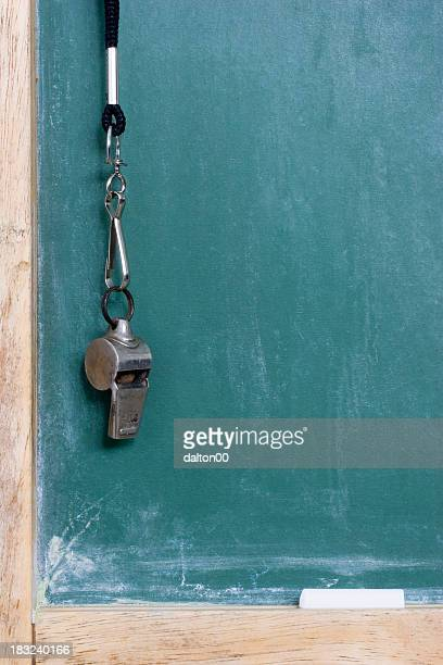 A whistle hanging on the left side of a green chalkboard