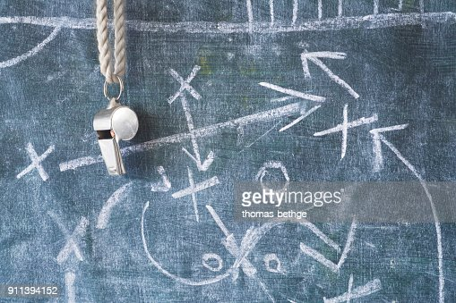 whistle of a soccer or football referee / coach on black board with tactical diagram : Stock Photo