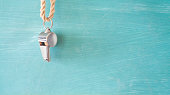 whistle of a soccer coach or referee on green painted background. Soccer symbol, good copy space
