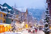 Whistler's world class pedestrian village filled with shops, hotels and restaurants blanketed with fresh snow at dusk