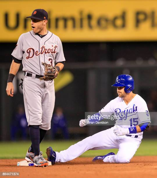 Whit Merrifield of the Kansas City Royals slides into second after hitting a double and Ian Kinsler of the Detroit Tigers waits for the ball during...