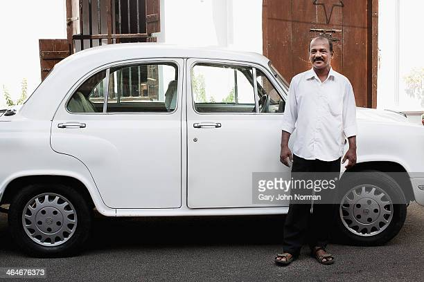 White Ambassador taxi car and driver