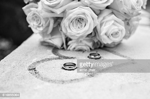White and black flowers and rings on frozen surface : Stock Photo