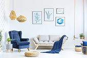 White and blue living room with sofa, armchair, lamp, posters