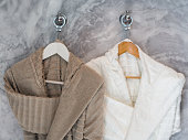 White and brown Clean bathrobes hanging on hanger