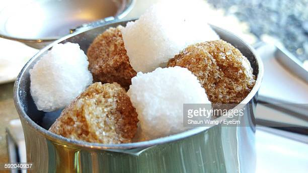 White And Brown Sugar Cubes In Cup