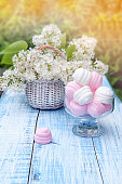 White and pink marshmallows in round glass vase with a basket of delicate white lilac.