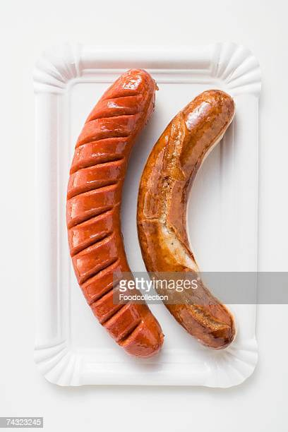 White and red sausages on a paper plate