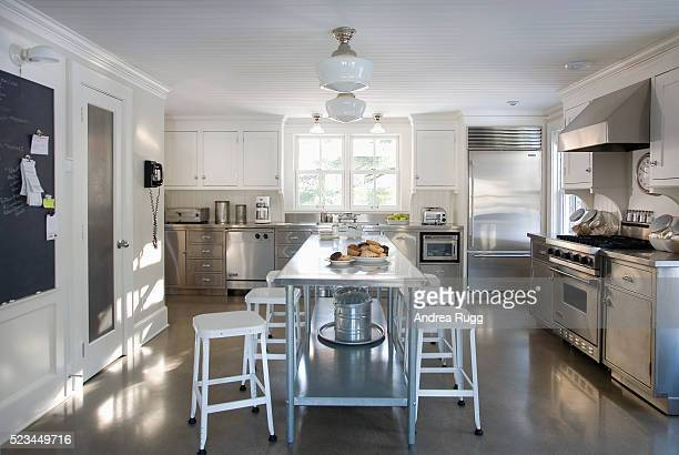 White and Stainless Steel Kitchen with Cement Floor