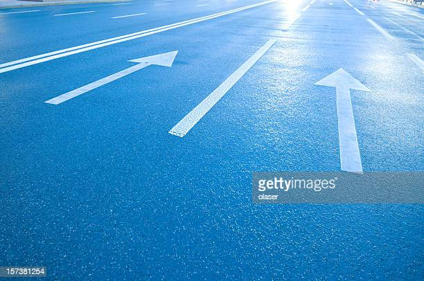 White arrows and lines on blue road