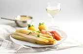Juicy white asparagus dish with potatoes and ham on a white plate, sauce hollandaise and wine blurred in the bright background, copy space, selected focus, narrow depth of field