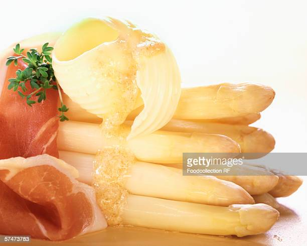 White asparagus with smoked ham and melting butter curl