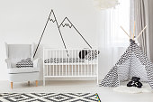 White baby room with cot, armchair and play tent