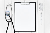 White background with medical tools. Empty sheet of white paper centered.