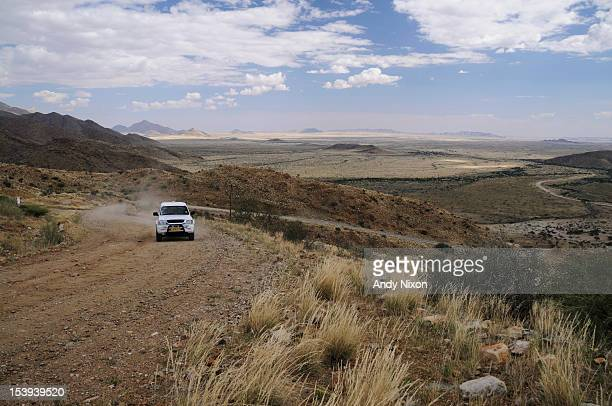 White bakkie driving up gravel road, Remhoogte Pass, Windhoek, Central Region, Namibia